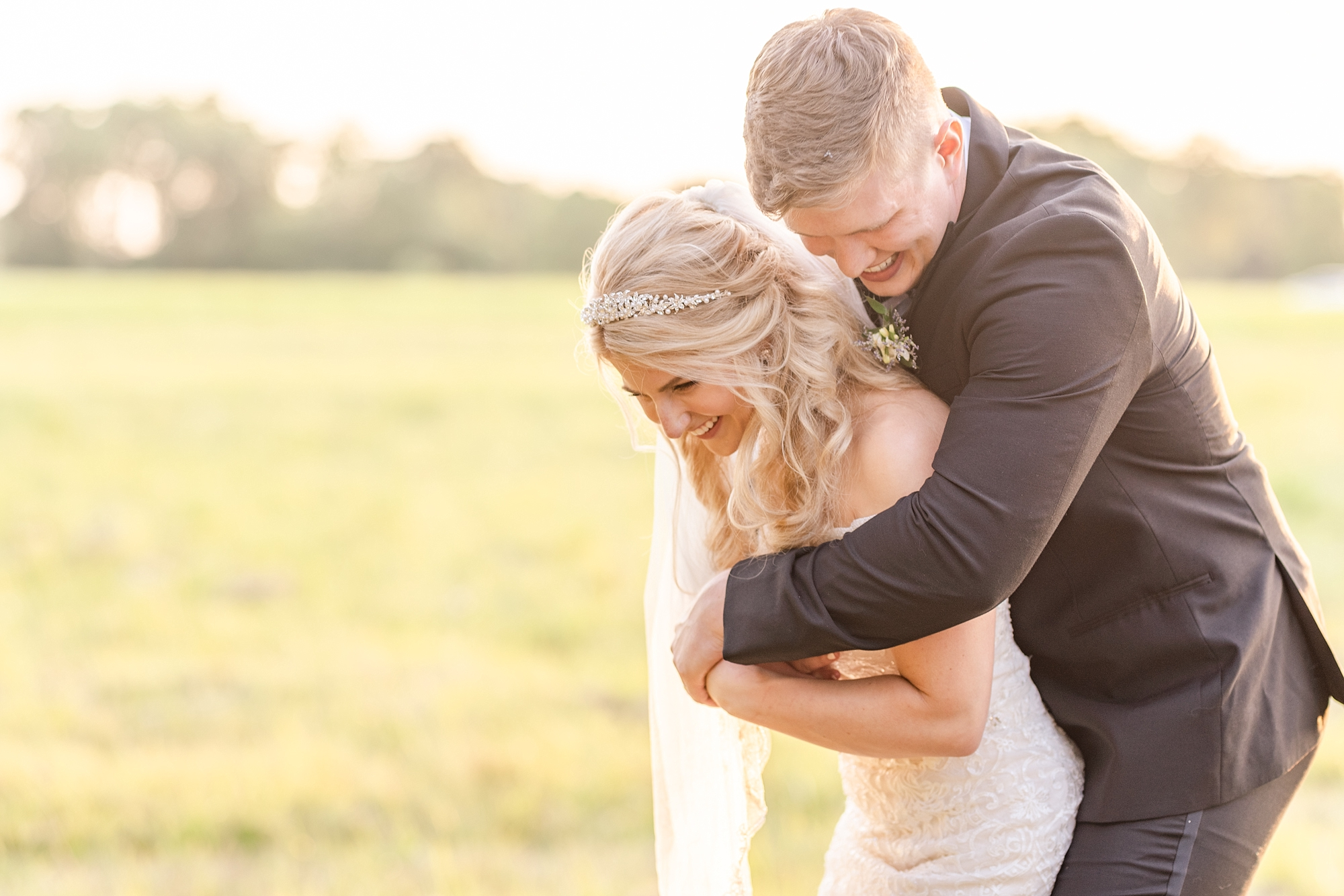 bride and groom laugh while hugging during wedding portraits in Ohio