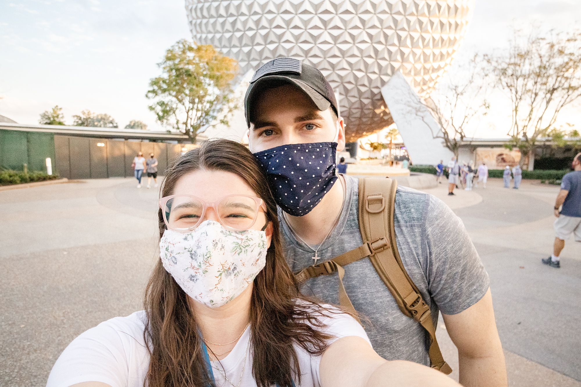 married couple in masks poses in front of Spaceship Earth