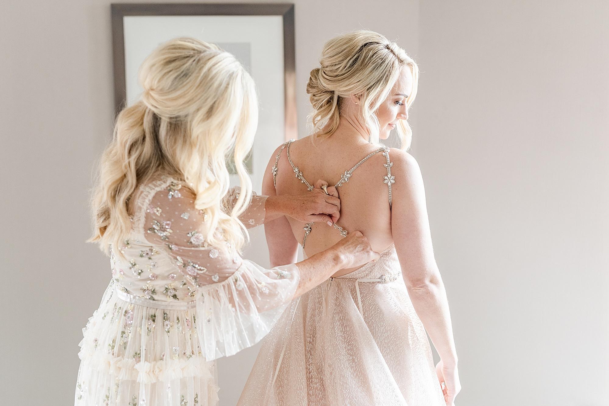 mother of bride adjusts gown for bride